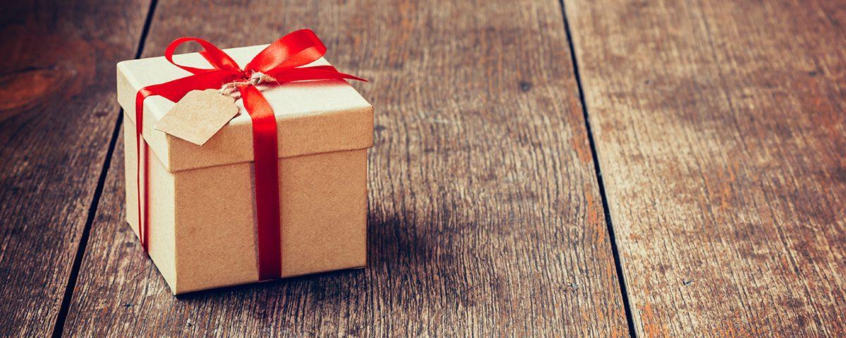 Prezent na drewnianej podłodze - W co zapakować prezent - nie tylko w Walentynki