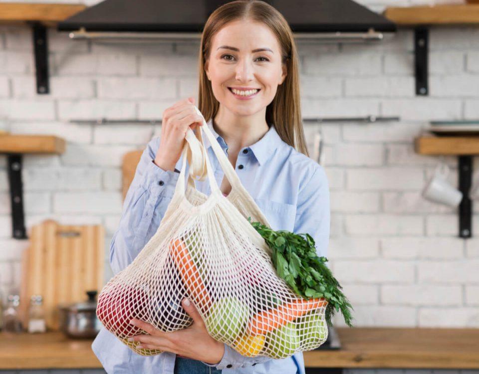 Uśmiechnięta kobieta z siatką pełną zakupów - Eko wybory - czyli jak dbać o naszą planetę