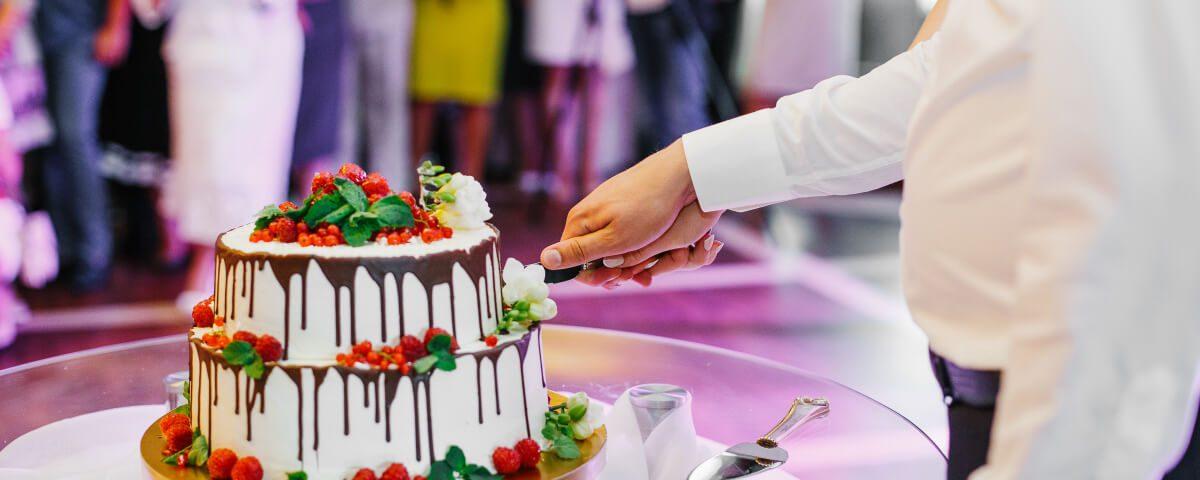 Młoda para kroi tort weselny. W co zapakować tort i inne produkty cukiernicze