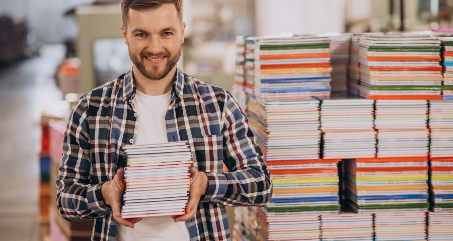 Mężczyzna z zeszytami. Czy miejsce papieru w gospodarce jest zagrożone?