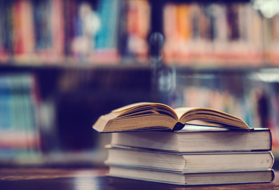 Otwarta książka w bibliotece. Ebook czy książka papierowa - co jest bardziej eko