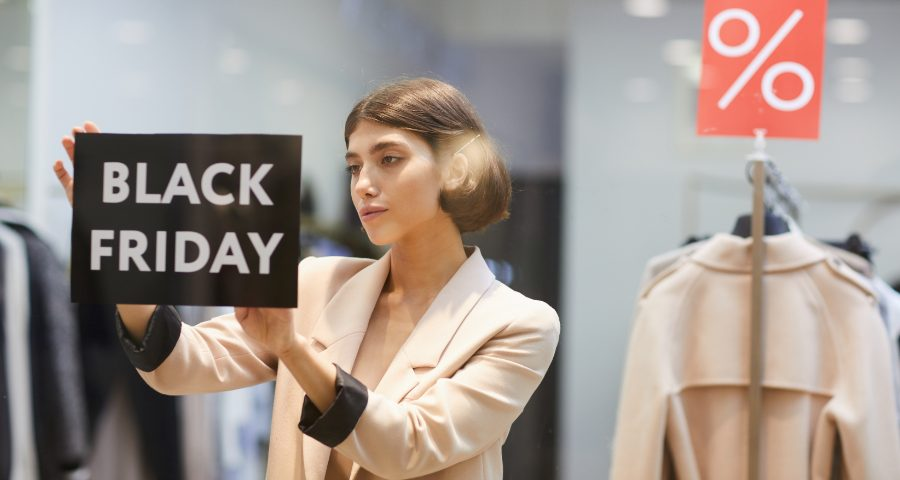 Sprzedawczyni wywiesza informację o Black Friday. Jak przygotować sklep na Black Friday.